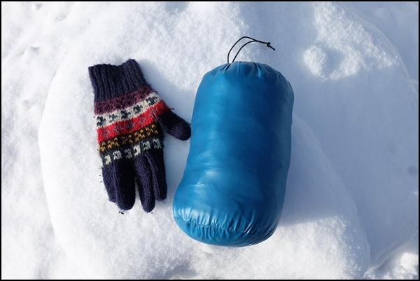 Daunenjacke im Beutel - mit Handschuh zum Größenvergleich