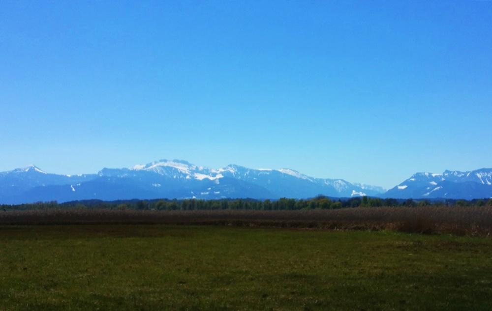 Das bayrische Alpenvorland. Platt, dann schneebedeckte Berge.