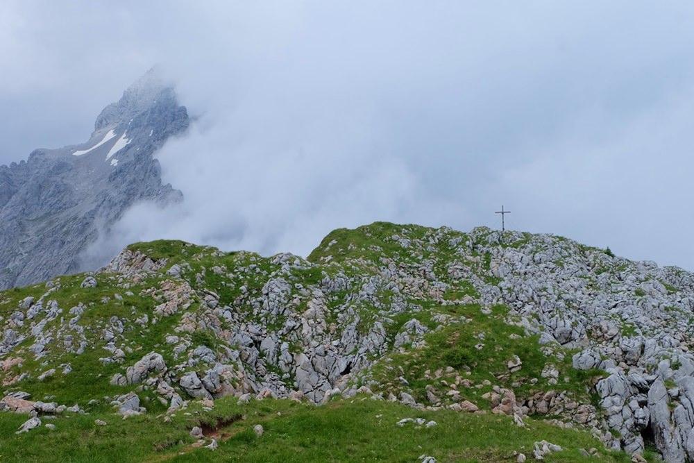 Gipfelkreuz in Sicht, zwischen dahinziehenden Wolken zwischen Hirschwiese und Watzmann