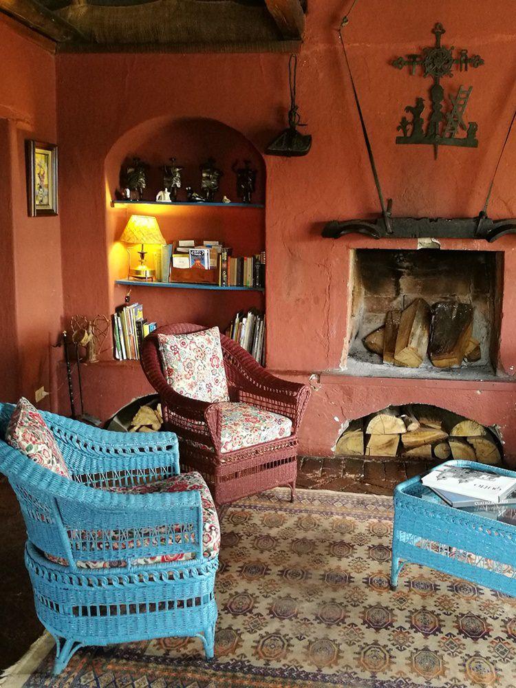 Gemütliches Wohnzimmer mit Kamin und Korbstühlen in der Hacienda | Ecuador