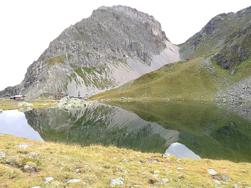 Spiegel-Bild. Kleine Hütte unter großen Felsen am Obstanser See | Karnischer Höhenweg, Osttirol