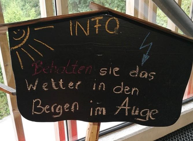 Schild mit der Aufschrift: Behalten Sie das Wetter in den Bergen im Auge